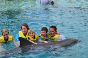 Family in dolphin pool
