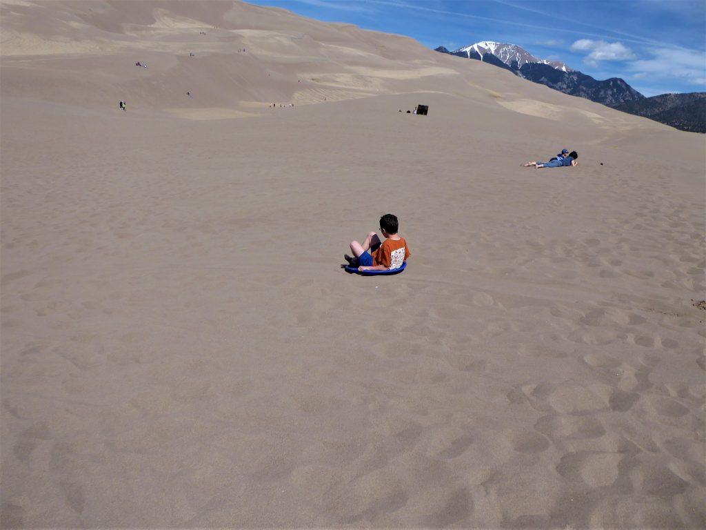 Great Sand Dunes boy sledding